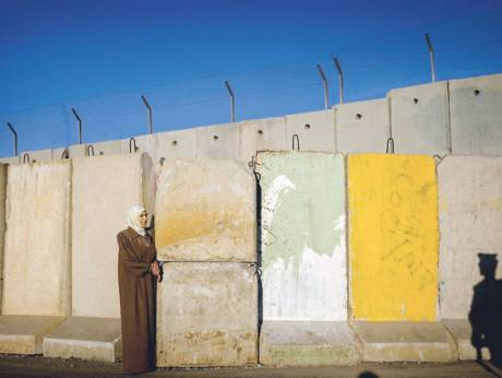A Palestinian woman stands next to a section of