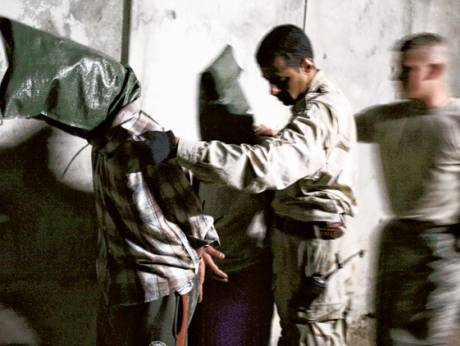 A US Army soldier, right, assists an Iraqi Army soldier escorting two hooded men detained