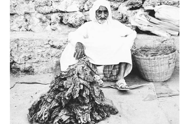 a-traditional-seller-displays-his-pile-of-tobacco-leaves-in-bur-dubai-in-the-1980s