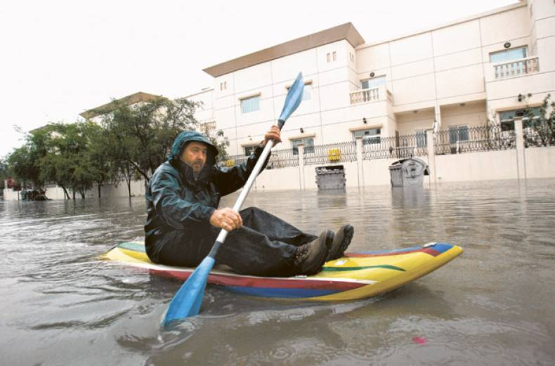 dubai-resident-dave-mccarthy-paddles-his-raft-down-a-flooded-street-in-urban-dubai