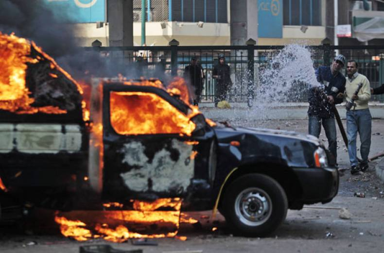 people-try-to-extinguish-a-police-car