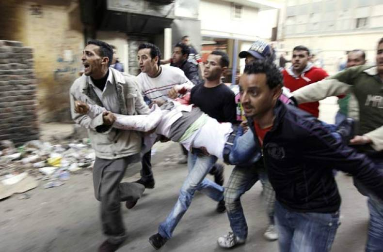 egyptians-carry-an-injured-protester-during-clashes-with-anti-riot-police-in-cairo