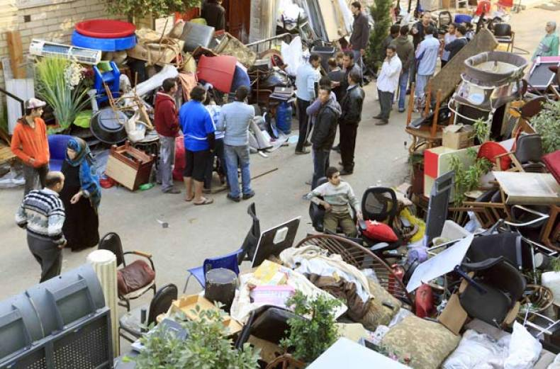 egyptian-volunteers-guard-looted-goods-confiscated-from-looters-at-a-street-in-cairo