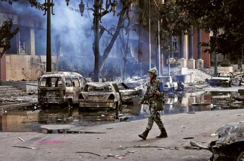 a-soldier-walks-in-a-street-with-burnt-out-vehicles-in-central-cairo