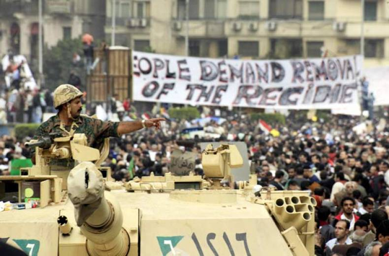an-egyptian-army-soldier-gestures-in-front-of-the-crowd-gathering-in-tahrir-square-in-cairo