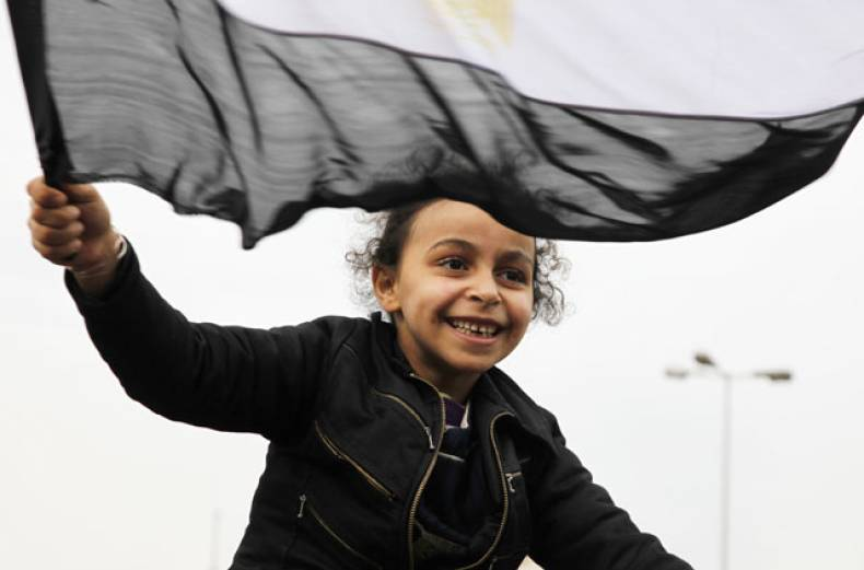 a-girl-waves-her-national-flag-as-anti-government-protestors-gather-in-tahrir-square