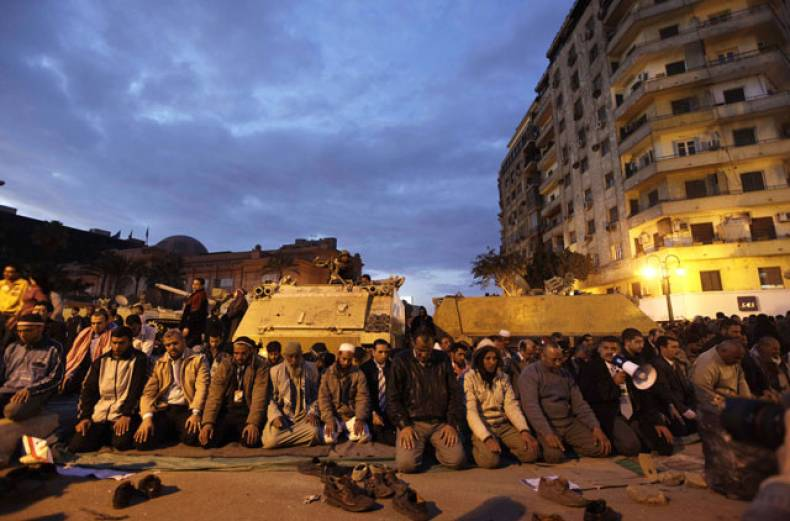 egyptian-protesters-pray-in-front-of-a-tank