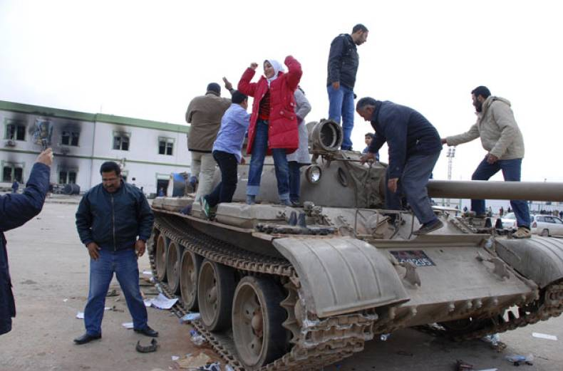 residents-stand-on-a-tank-inside-a-security-forces-compound-in-benghazi