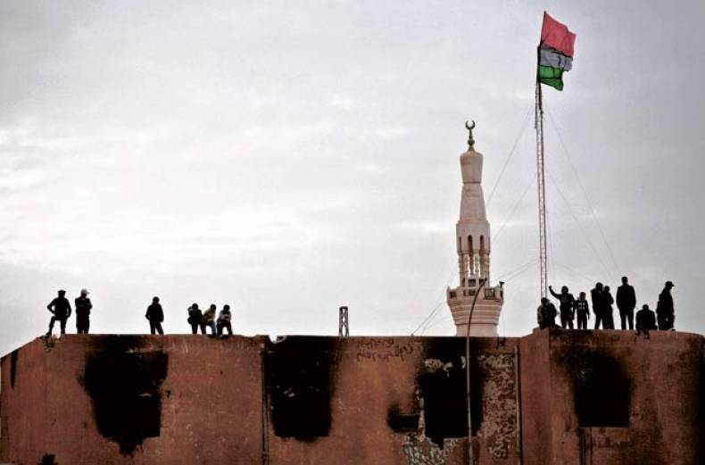 the-former-royal-libyan-flag-flies-above-an-abandoned-and-damaged-police-station
