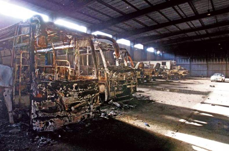 burnt-out-buses-belonging-to-the-security-forces-of-muammar-gaddafi-are-lined-up-in-a-hangar