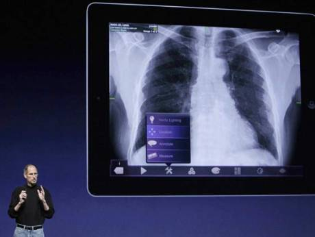 Apple Inc. Chairman and CEO Steve Jobs stands under images of the iPad 2 at an Apple event