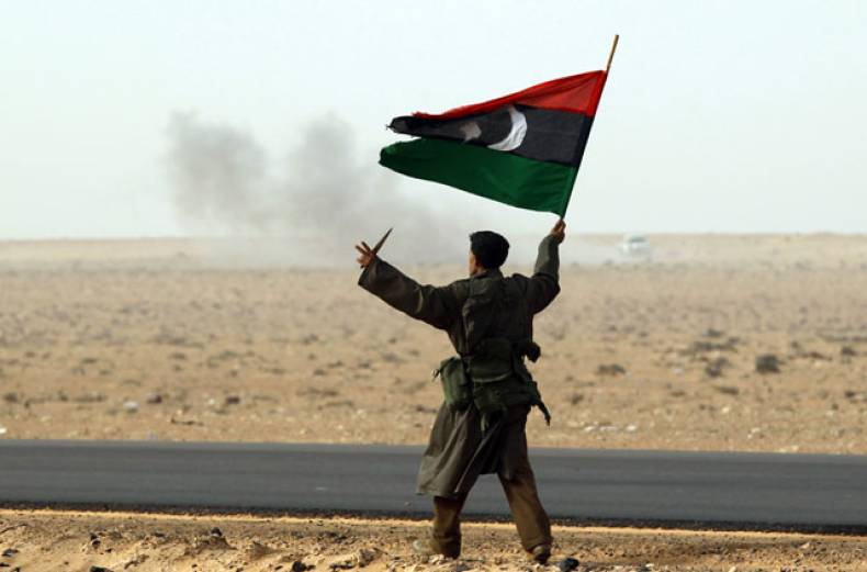 a-rebel-fighter-holds-a-kingdom-of-libya-flag