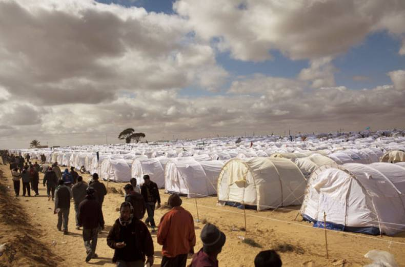 men-walk-next-to-their-tents-in-a-refugee-camp-at-the-tunisia-libyan-border