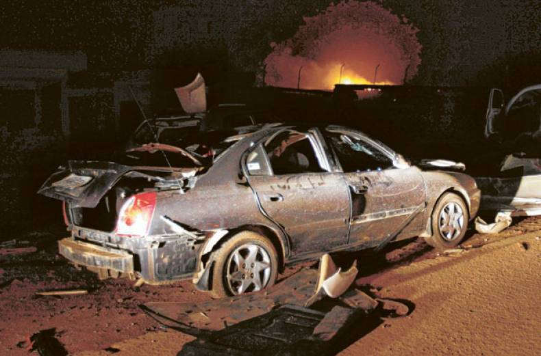 a-destroyed-car-sits-near-a-burning-ammunition-storage-facility