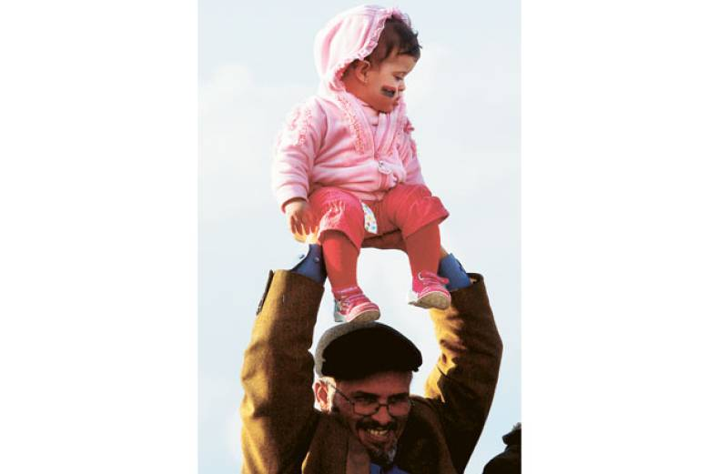 a-man-lifts-a-toddler-during-a-rally-at-the-benghazi-courthouse