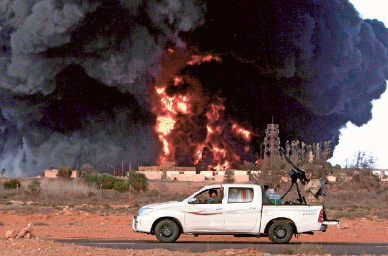 rebels-drive-past-a-burning-al-sedr-oil-terminal