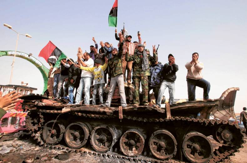 people-celebrate-atop-a-destroyed-tank
