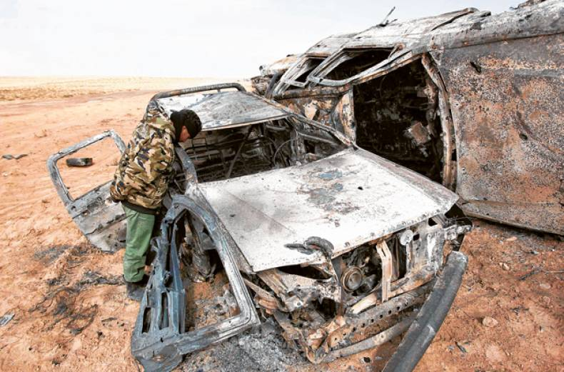 a-rebel-fighter-looks-at-cars-burnt