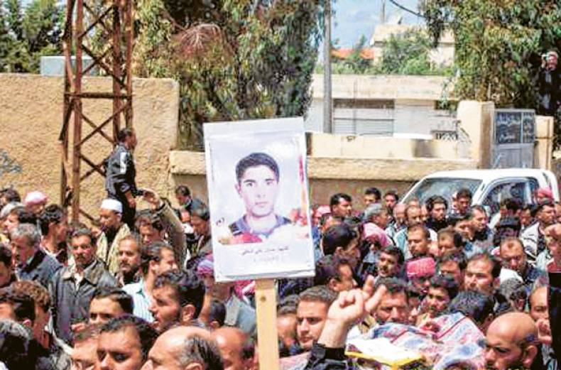 syrian-anti-government-protesters-carry-a-poster-of-a-slain-activist-during-a-funeral-procession