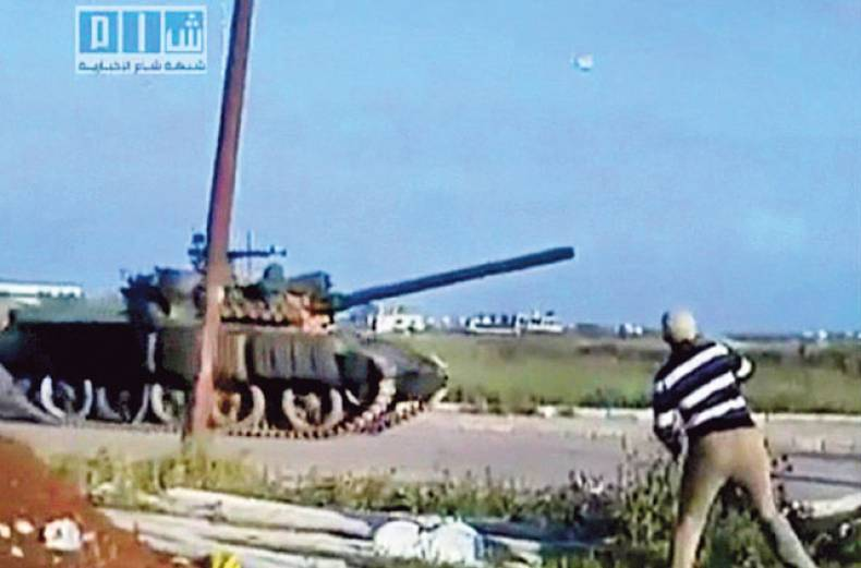 a-man-throws-an-object-at-a-tank-in-daraa