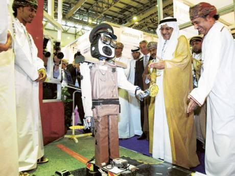 Humaid Mohammad Al Qutami, Minister of Education, admires an exhibit at a pavilion