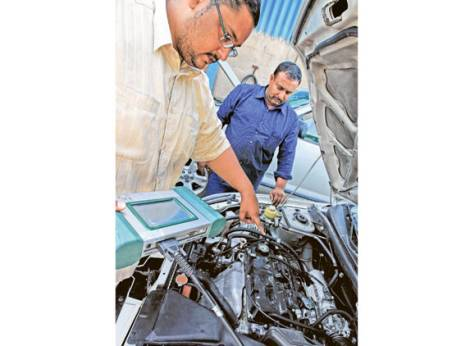 Rizwan Ali (left) uses a diagnostic computer to test a car's engine