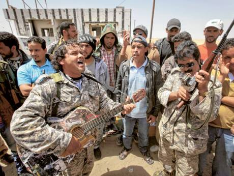 Amateur musician Masoud Abu Assir plays the guitar to entertain rebel fighters