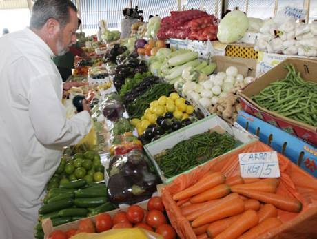 A customer selects vegetables at the Mina fruits and vegetable market in Abu Dhabi