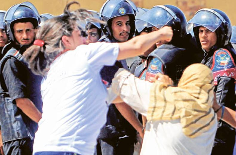 egyptian-riot-police-look-at-a-supporter-of-egypt-s-former-president-hosni-mubarak-clashing