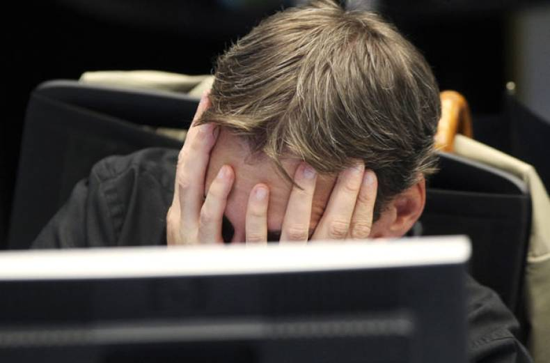 a-broker-covers-his-face-behind-his-screen-at-the-stock-market-in-frankfurt-germany
