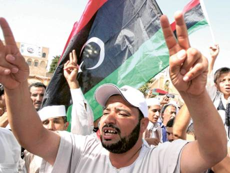 A man flashes the victory sign and others wave the national flag as they celebrate the fall of Sirte
