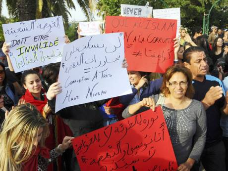 Tunisians hold up banners during a protest against the moderate Islamic party Al Nahda in Tunis