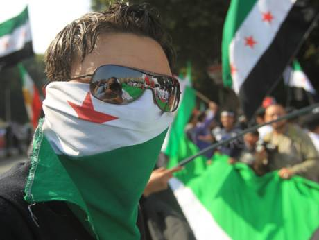 Pro-democracy protesters, waving pre-Baath era Syrian flags  outside the Arab league headquarters in