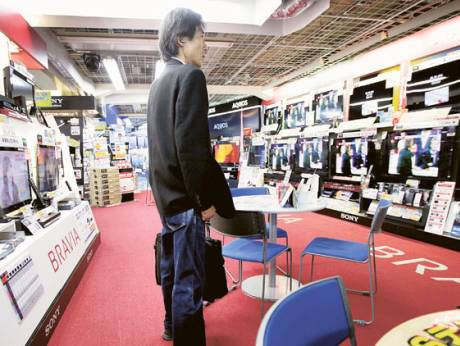 A customer looks at Sony Corp's Bravia televisions at an electronics store in Tokyo