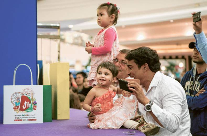 a-family-takes-a-break-from-shopping-during-dsf-at-deira-city-centre
