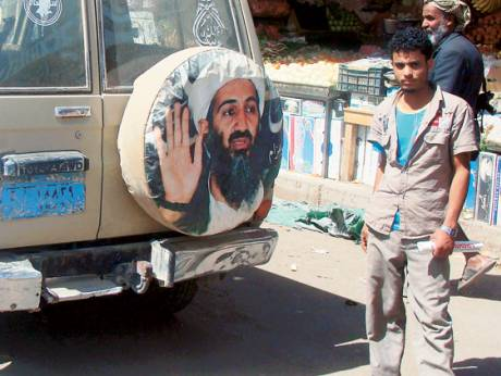 A passing vehicle flaunts Osama Bin Laden's image in a street of Yemen's Rada town