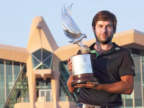 Robert Rock of England displays the trophy after winning the Abu Dhabi Championship