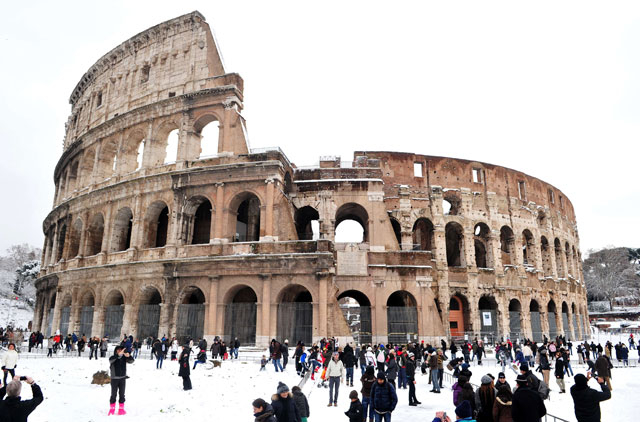 People standing in front of the Colosseum covered with snow in Rome