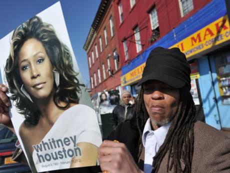 A woman carries a poster of Whitney Houston