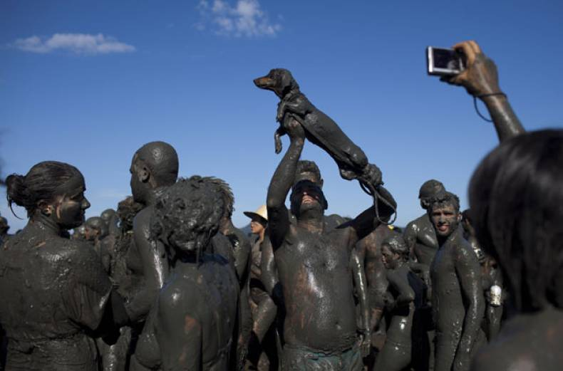 a-man-covered-in-mud-holds-up-his-mud-covered-dog-as-another-reveler-takes-a-picture