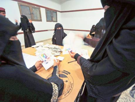 Electoral officials count ballots at a polling station in Sana'a