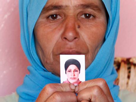 Zohra Filali, mother of rape victim Amina Filali, holds her photo