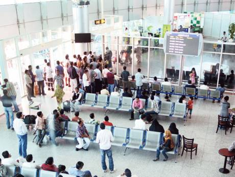 People waiting in the arrivals area of Sharjah International Airport